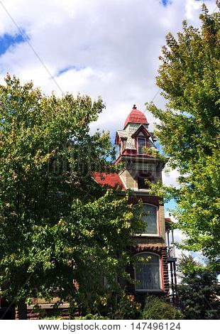 Elegant and stately this Queen Ann Victorian home is brick and stone. Square tower is red wood with four dormers and four sided dome top.