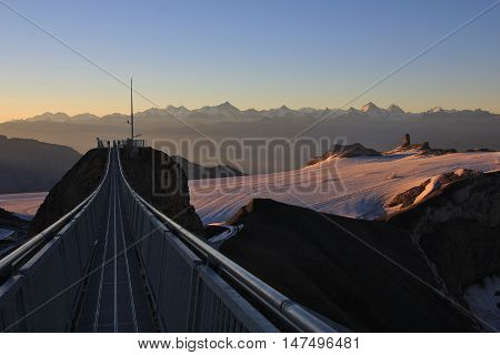 View from Sex Rouge. Glacier de Diablerets at sunrise. Suspension bridge connecting two peaks. Summer scene in the Swiss Alps.