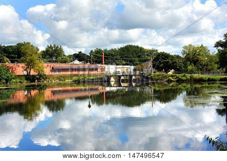 Stoughton Dam is reflected in the calm and peaceful waters of the Yahara River. This small Wisconsin town has buildings clouds and blue skies reflected.