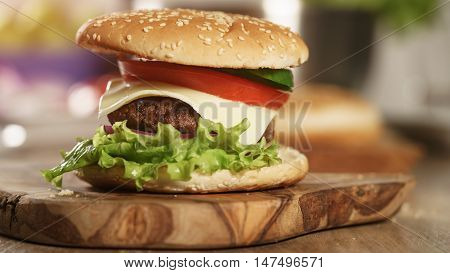 fun made fresh burger with marble beef, cheese and vegetables on olive board, shallow focus
