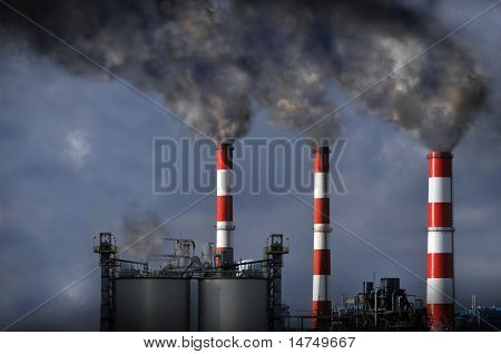 Industrial smokestacks blowing dark smoke into the atmosphere