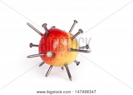 Apple stuck with lots of iron nails isolated on white background