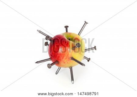Apple stuck with iron nails isolated on white background