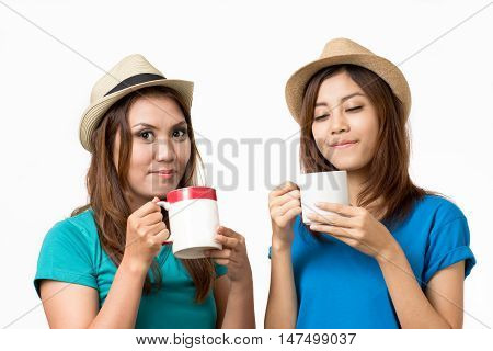 Two woman are drinking tea and coffee.