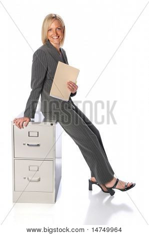 Businessman holding folder sitting on file cabinet