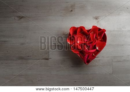 Rose Petals In Heart Shaped Bowl On Wood From Above