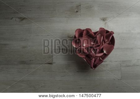 Overhead Of Rose Petals Filling Heart Shaped Bowl