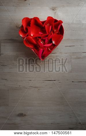 Overhead Of Rose Petals In Heart Shaped Bowl On Wood