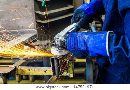 worker grinding metal in  manufacturing plant automotive part.