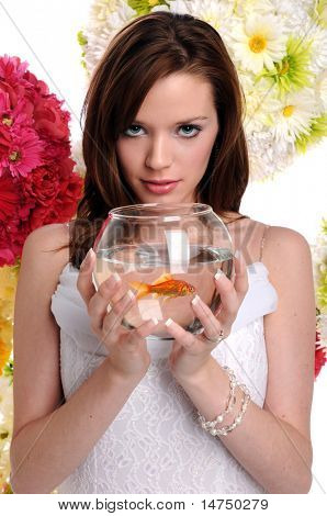 Beautiful young woman holding fishbowl with goldfish over background with flowers