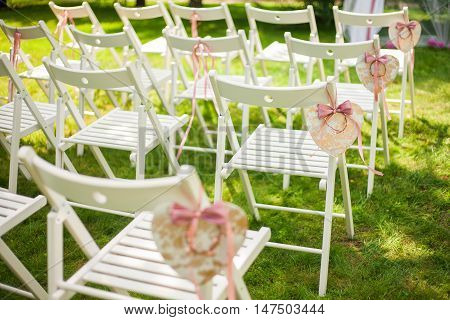 Beautiful place for outside wedding ceremony in city park. Many white wooden chairs decorated