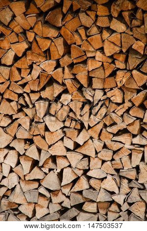 A stack of logs for a fire in a wood shed.