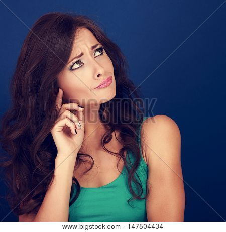 Concentrated Confused Beautiful Woman Thinking And Looking Up On Empty Space Blue Background. Curly