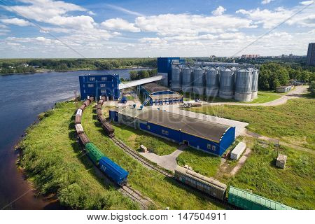 aerial view of freight railway station on the Bank of the river. It consists of a boot block on the left and 12 large tanks to the right. The station building is blue. Russia, 2106