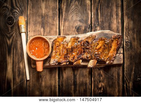 Barbecue pork ribs with spicy sauce. On a wooden table.