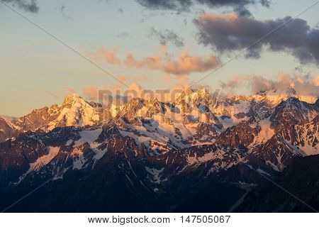 A colourful and partly clouded sunrise shot of Mont Dolent and Tour Noir two prominent peaks above the Argentière side of the Chamonix valley in the French alps.