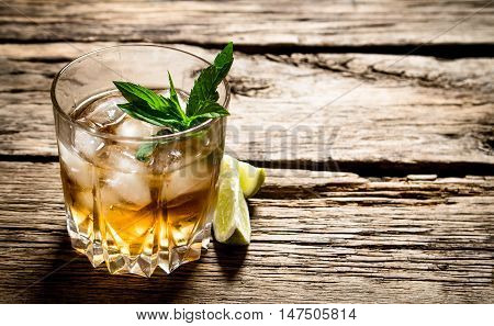 glass of rum with ice , lime and mint. On wooden background