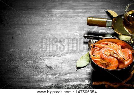 Shrimp with white wine and a corkscrew. On the black chalkboard