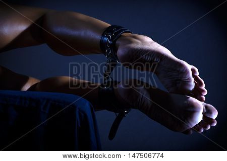 Low key photo of sexy female nude legs binded with cuffs against dark background horizontal view