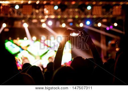 People makes photo with His smartphone on rock concert to share the moment with friends on social networks