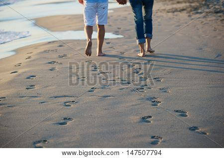 couple on the beach holding hands while walking