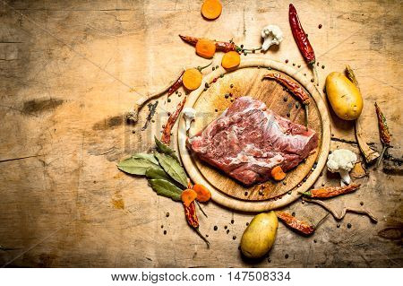 Ingredients for soup with pork. On wooden background.