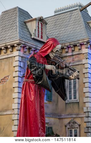 10th September 2016, Bad Dürkheim, folk festival 2016, Germany: Mysterious red hooded skeleton figure playing violin in front of a mystic castle in the amusement park