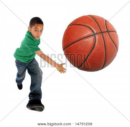 Young African American boy playing basketball - Selective focus on ball
