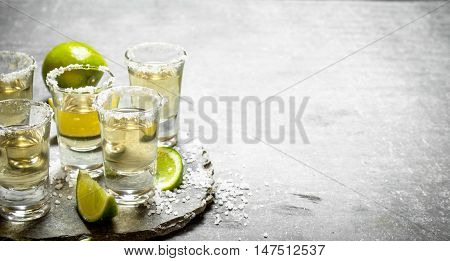 Tequila with lime and salt. On the stone table.
