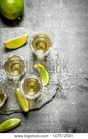Tequila shots with lime and salt . On the stone table.