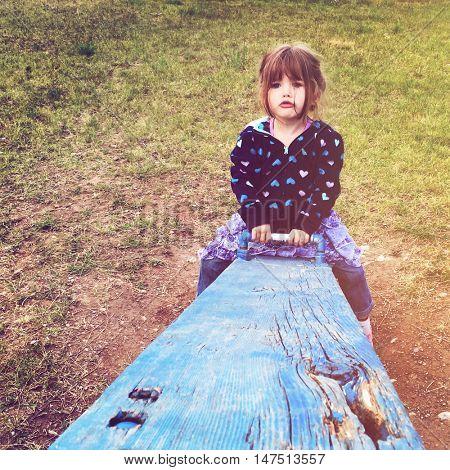 Beautiful little girl on see saw