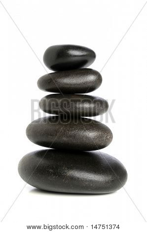 Fives black stones stacked upon each other isolated over white background
