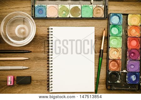 Workstation concept top view : Water color,brush,pen,marker,pencil,rubber,sharpener,glass of water,book and color pencil on wooden background