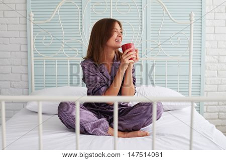 Brown-haired smiling pretty lady in pajamas is drinking her morning coffee sitting on bed and looking in the window