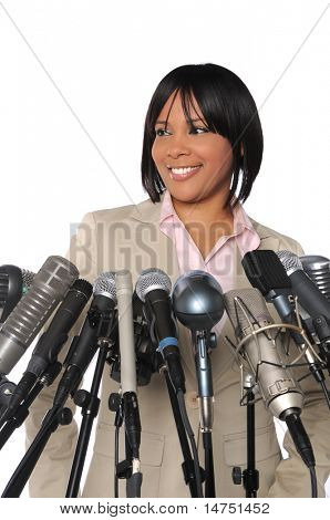 African American woman speaking in front of multiple microphones
