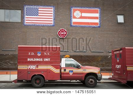 NEW YORK - SEPT 9 2016: Firetrucks parked under the wreath of red flowers shaped as FDNY badge on the Memorial Wall at the FDNY Ten House fire station before the 15th anniversary of the terror attack.