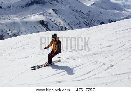 skier turning down the mountain in winter