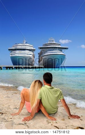 Man and Woman relaxing on beach with cruise ships in background