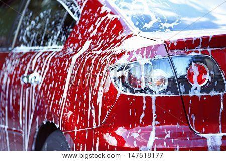 Car washing concept. Red car in foam
