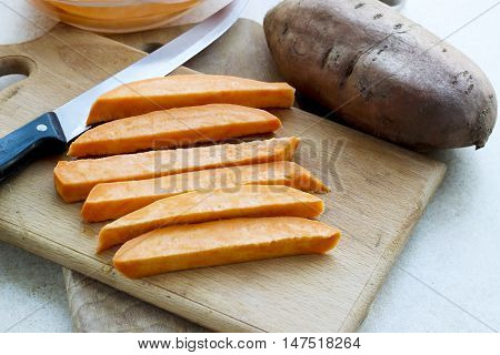 Sweet Potatoes Slices On A Wooden Cutting Board