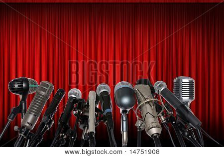 Microphones in front of red curtain