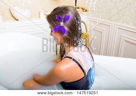 Milk is pouring on women shoulders in bathtub