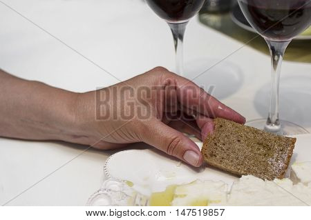 Female hand with a slice of bread in focus two glasses of red wine in the blurred background