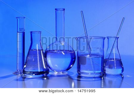 Laboratory glassware in blue light over reflective table