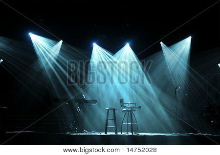 Escenario con luces y micrófonos listos para concierto