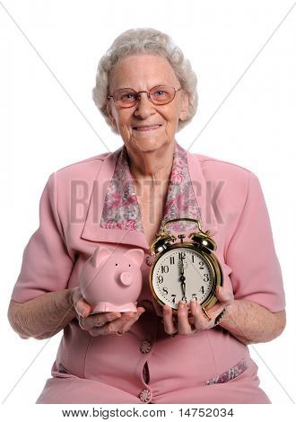 Senior woman holding piggy bank and clock isolated over white