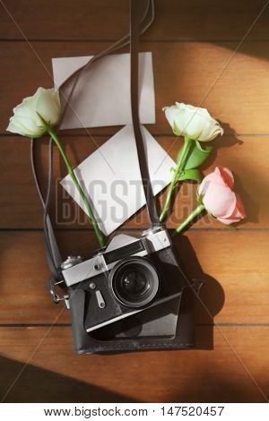 Vintage camera, photos and beautiful roses on wooden table