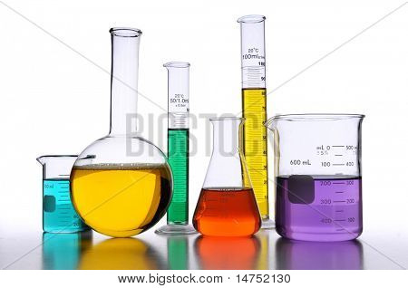 Laboratory glassware with liquids of different colors over white background