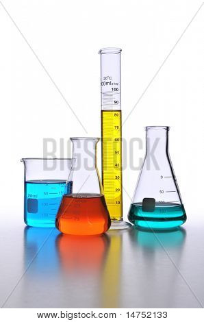 Laboratory glassware with color liquids over white with surface reflections
