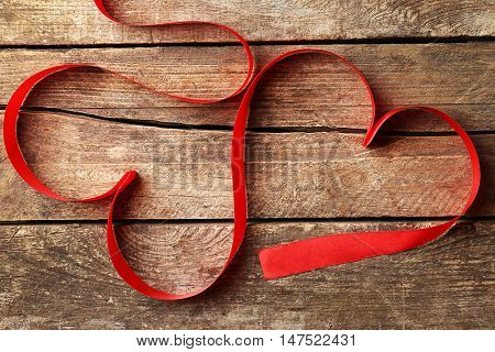 Two hearts made of red ribbon on wooden background